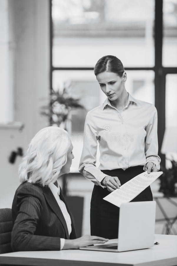 Businesswoman and her boss working with documents in office stock images
