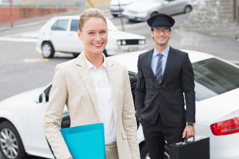 Businesswoman and her chauffeur smiling at camera. Outside the car royalty free stock images