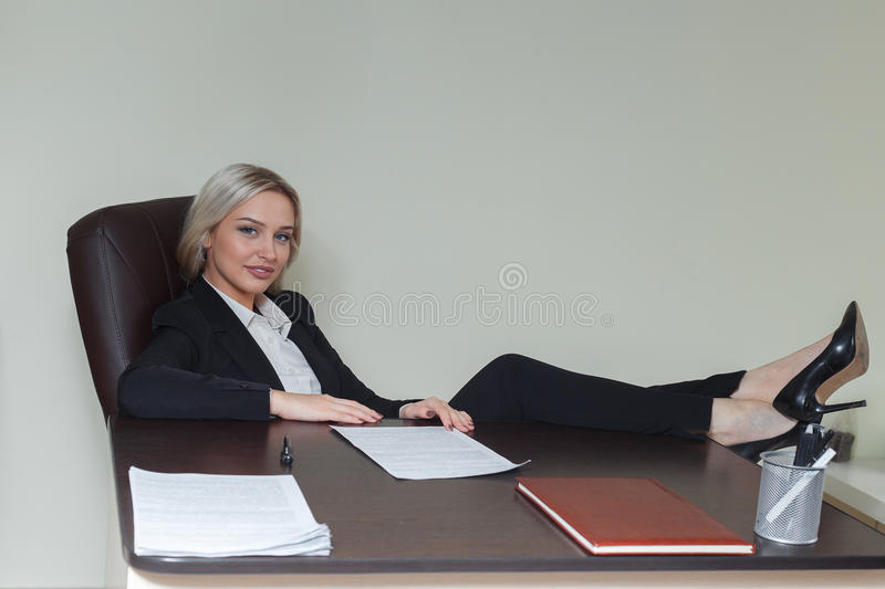 Businesswoman with her foot on the desk. royalty free stock image