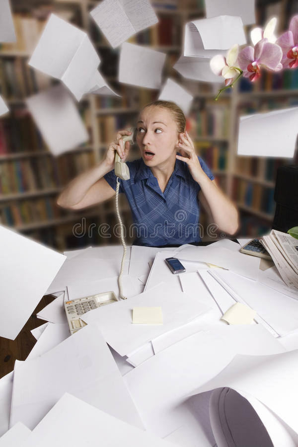 Businesswoman in her office and flying paper sheet royalty free stock photo
