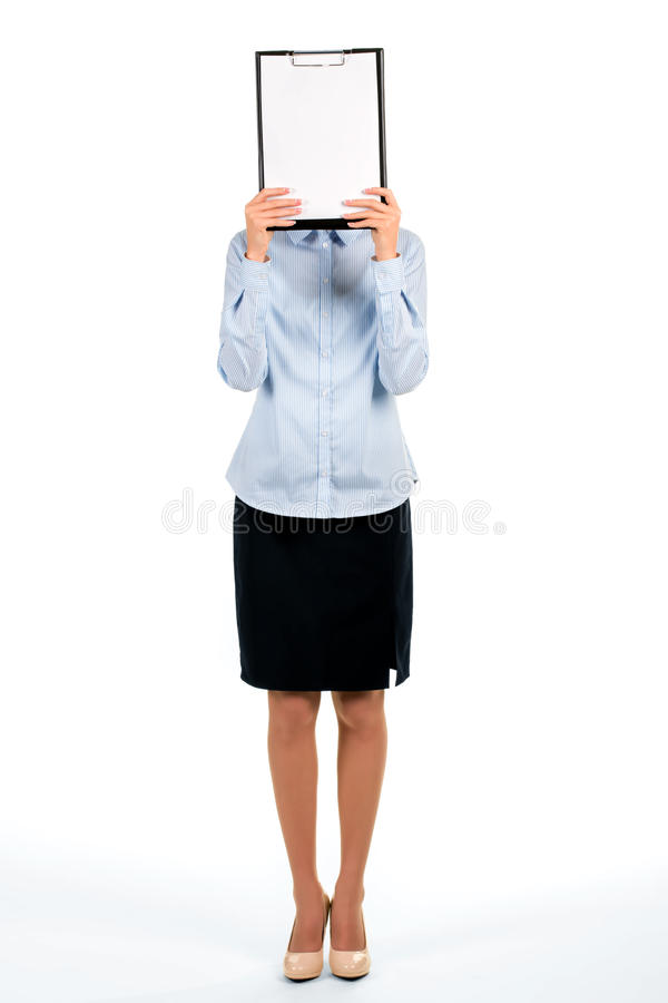 Businesswoman hiding face behind clipboard. royalty free stock photography