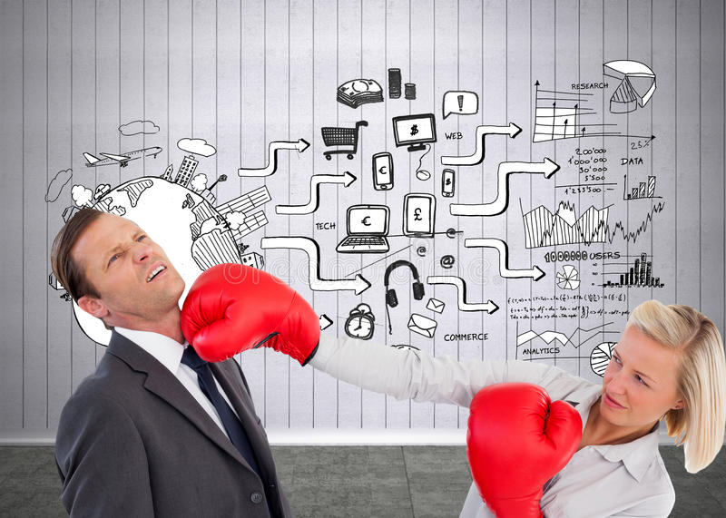Businesswoman hitting colleague with her boxing gloves. Composite image of businesswoman hitting colleague with her boxing gloves stock photo