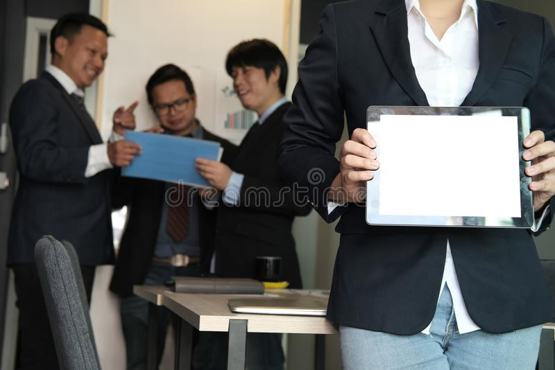 Businesswoman hold tablet at workplace. young woman shows inform stock photography