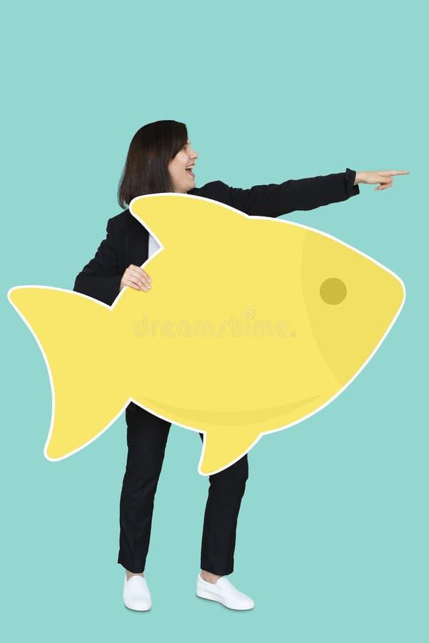 Businesswoman holding a big fish stock photo