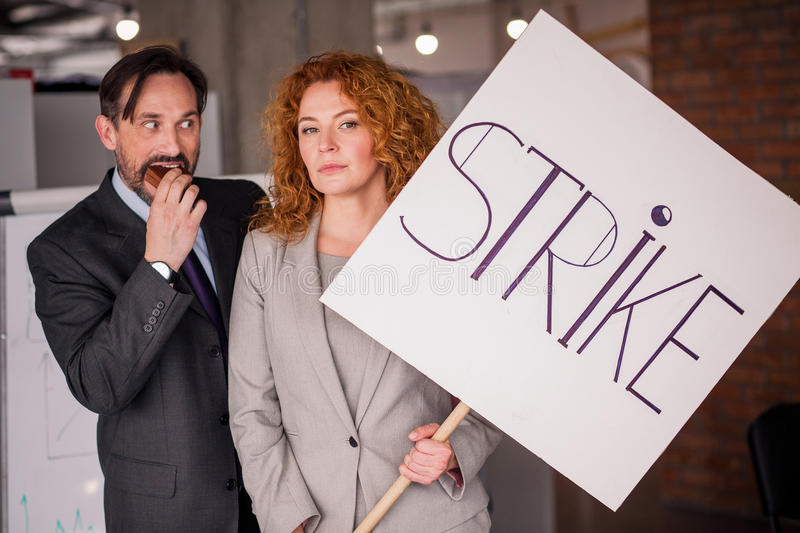 Businesswoman holding big poster with word strike. stock image