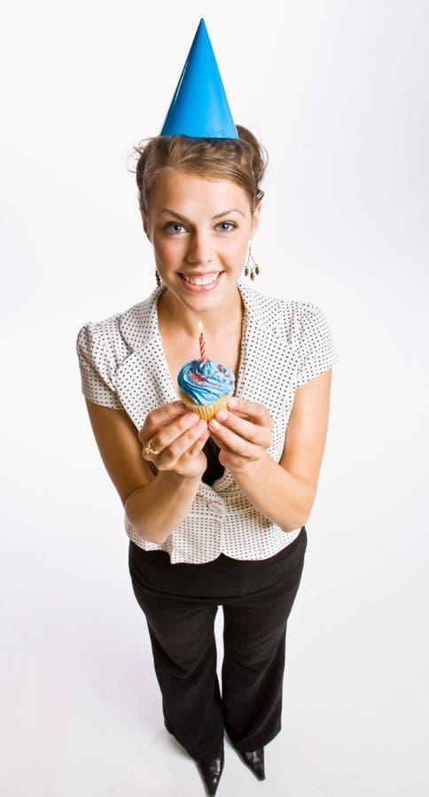 Businesswoman holding birthday cupcake. Wearing birthday hat stock image
