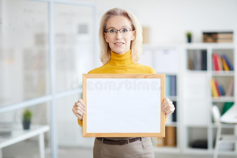 Businesswoman Holding Blank Sign. Waist up portrait of smiling mature businesswoman holding blank sign while posing in modern office, copy space stock images