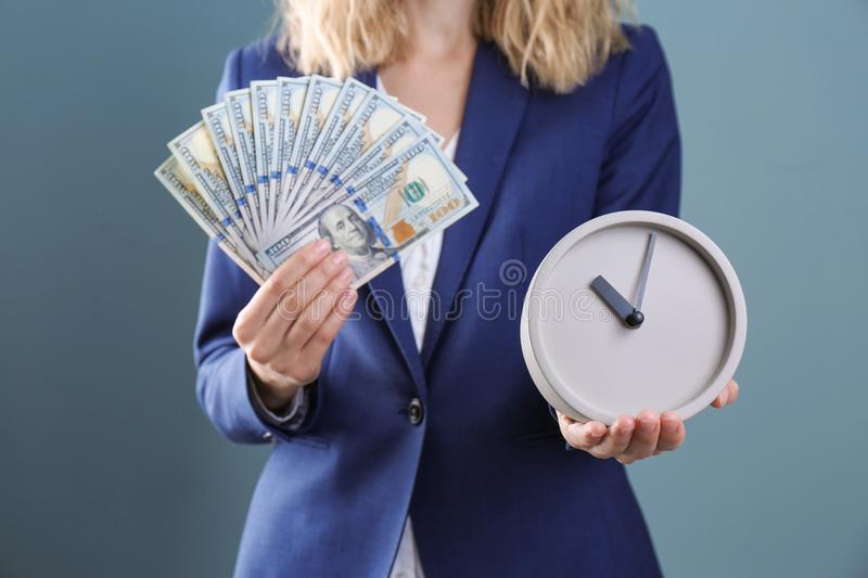 Businesswoman holding clock and money on color background. Time management royalty free stock image