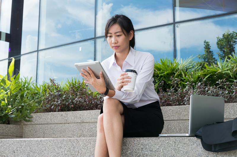 businesswoman holding digital tablet & coffee outside office building. beautiful young asian woman with tea sitting outdoors. fem royalty free stock photos
