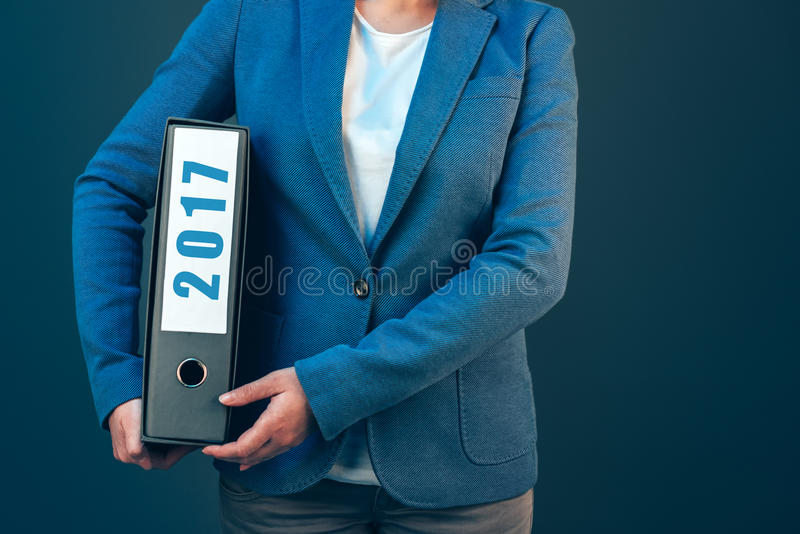 Businesswoman holding 2017 document binder with archived files royalty free stock image