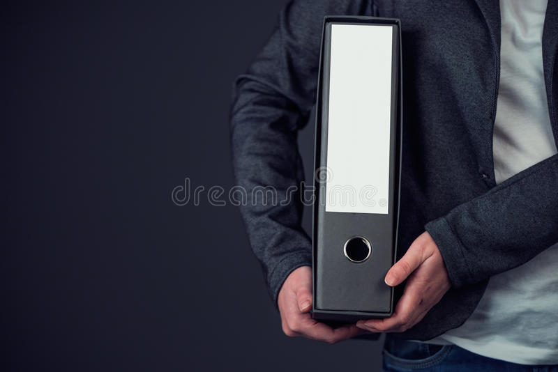 Businesswoman holding document ring binder with blank label as c. Opy space, female accountant or financial advisor archiving business documentation stock photo