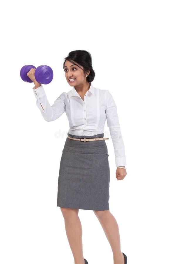 Businesswoman holding dumbbell stock photos