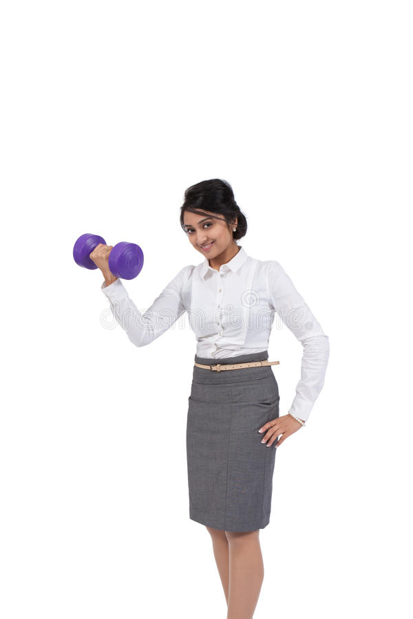 Businesswoman holding dumbbell stock photography