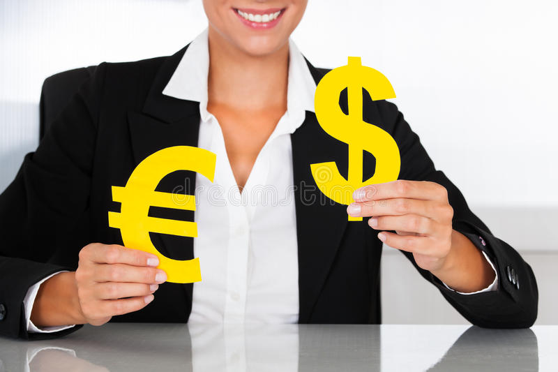 Download Businesswoman Holding Euro And Dollar Sign At Desk Stock Photo - Image: 34957212