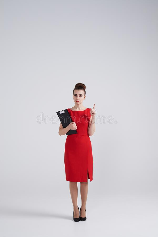 Businesswoman holding folder and pointing upward. Full-length portrait of businesswoman holding folder and pointing upward royalty free stock photos