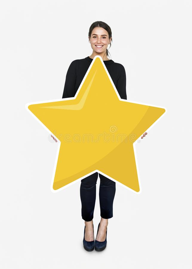 Businesswoman holding a golden star rating symbol royalty free stock image