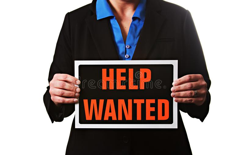 A businesswoman holding a help wanted sign. royalty free stock photos