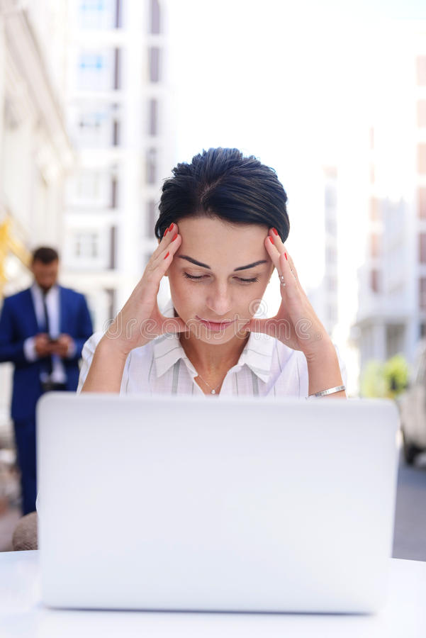 Businesswoman holding her head with hands stock image