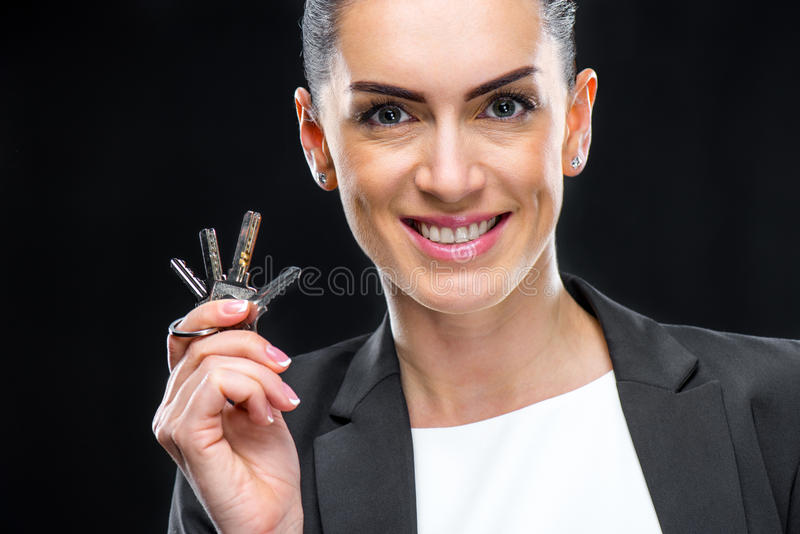 Businesswoman holding keys. Attractive businesswoman holding keys and smiling at camera royalty free stock photography