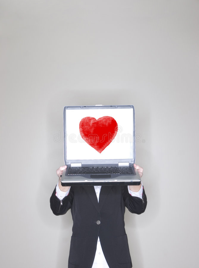 Businesswoman holding laptop with heart. Businesswoman holding her laptop high to show her work while wearing business clothes in an office with a Valentines Day stock photo