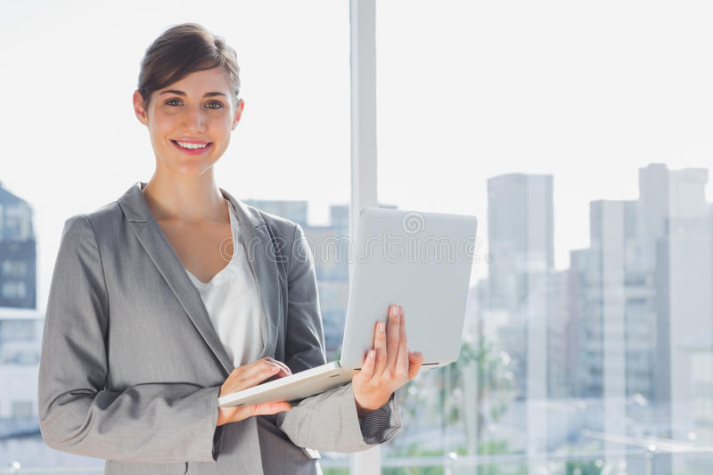 Businesswoman holding laptop and smiling at camera