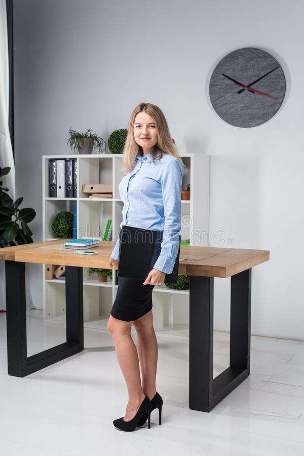 Businesswoman Holding Large File. young womanl standing in the office and holding folder. Portrait of young office worker holding stock image