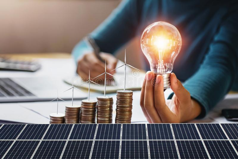 Businesswoman holding light bulb with turbine on coins and solar panel. concept saving energy and finance accounting. Money, electricity, lightbulb, save stock photo