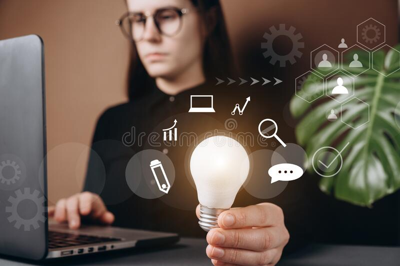 Businesswoman holding light bulbs with virtual icon diagram, ideas of new ideas with innovative technology and creativity. Selective focus royalty free stock photography