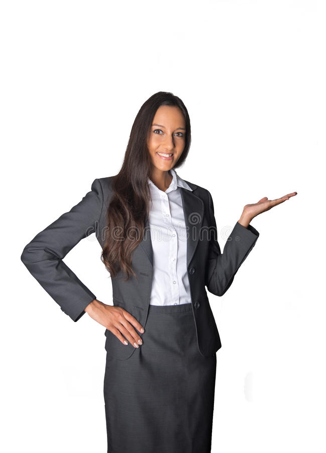 Businesswoman holding out her empty palm. Stylish Asian businesswoman standing holding out her empty palm for product placement, in welcome, or displaying stock photography