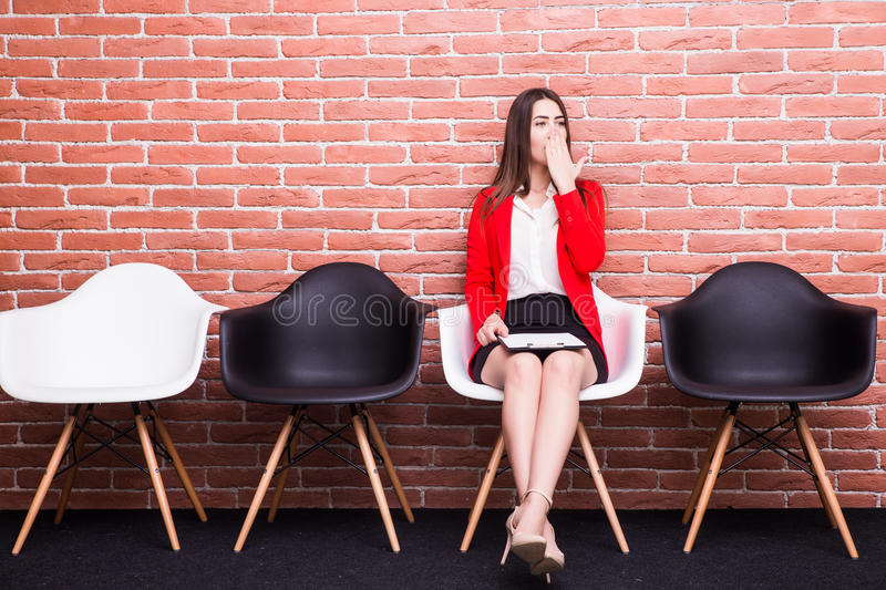 Businesswoman holding paper and looking away while sitting on chair. Bored young businesswoman holding paper and looking away while sitting on chair royalty free stock photography