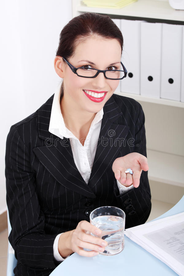 Businesswoman holding pills and water. royalty free stock photography