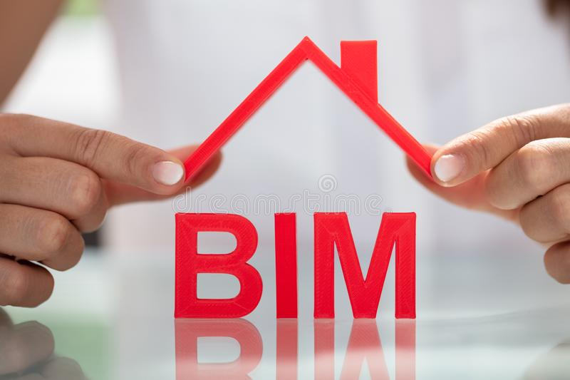 Businesswoman Holding Roof Over BIM royalty free stock photos