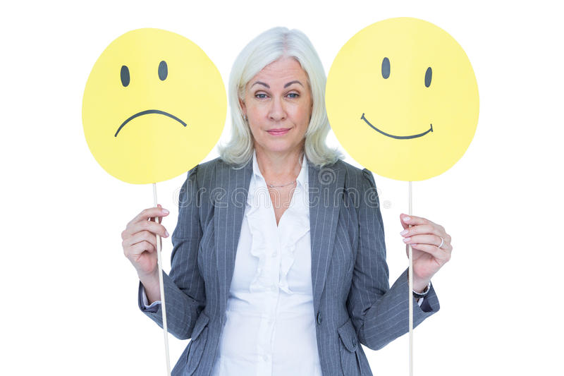 businesswoman holding a sad and a happy smiley stock photo