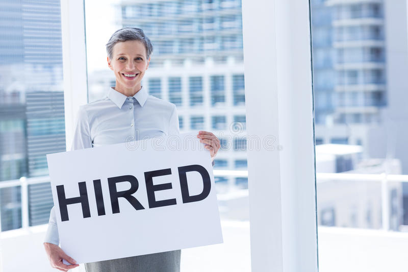 Businesswoman holding a signboard hired. In the office royalty free stock photography