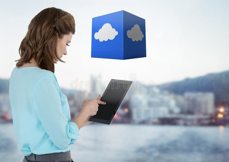 Businesswoman holding tablet with cloud cube with distant city background royalty free stock photography