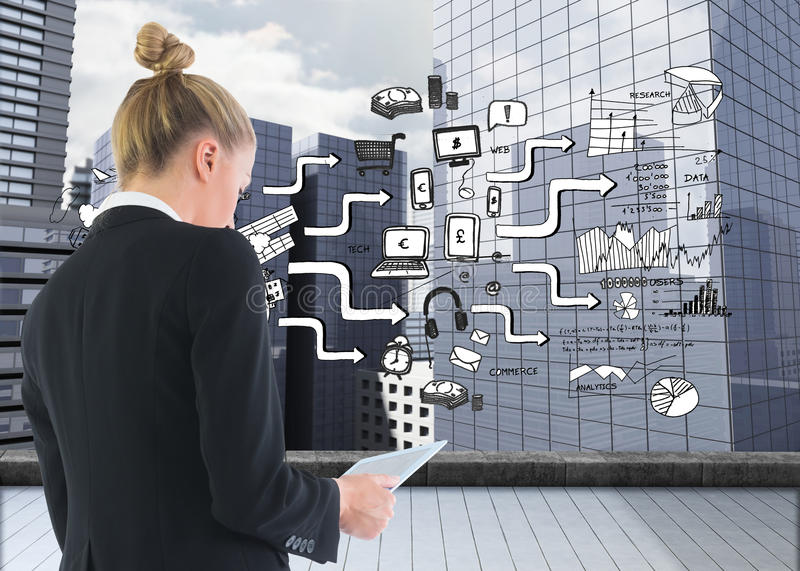Businesswoman holding tablet. Composite image of blonde businesswoman holding tablet stock photo
