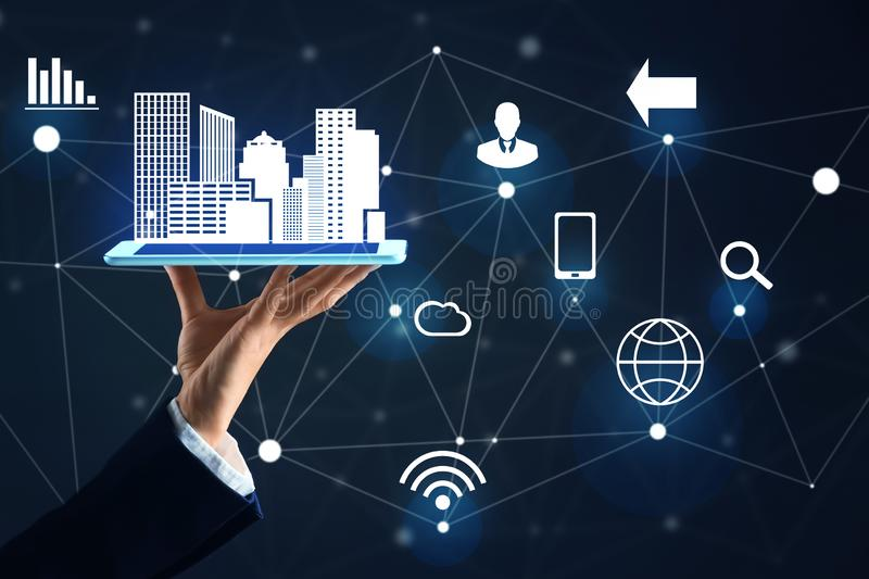 Businesswoman holding tablet PC with city model and icons on dark background. Internet concept stock image