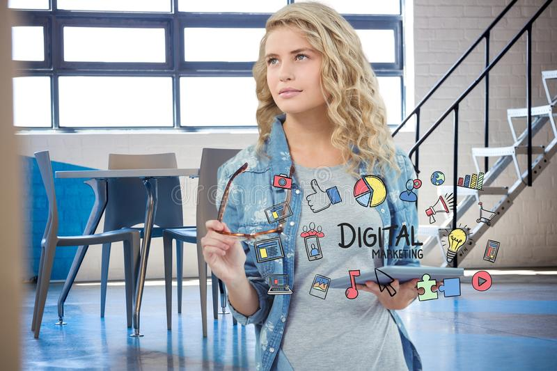 Businesswoman holding tablet PC surrounded by digital marketing text and icons. Digital composite of Businesswoman holding tablet PC surrounded by digital royalty free stock photography