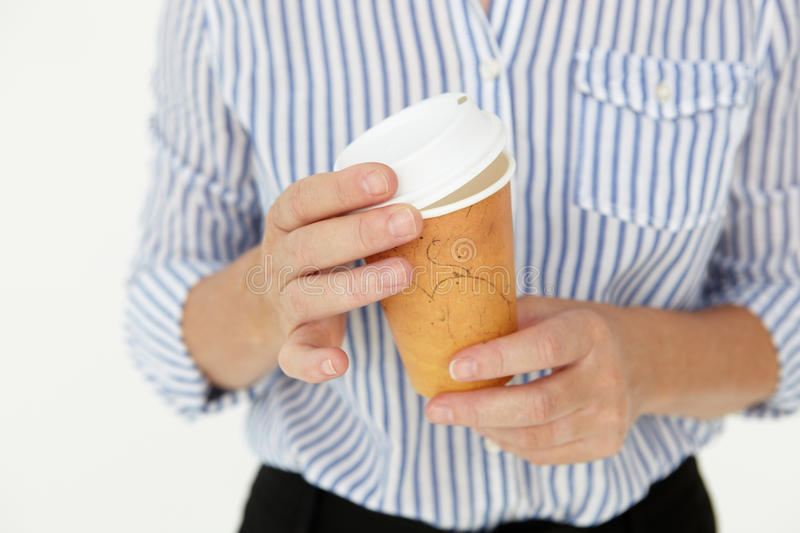 Businesswoman holding takeout coffee. At work royalty free stock photography