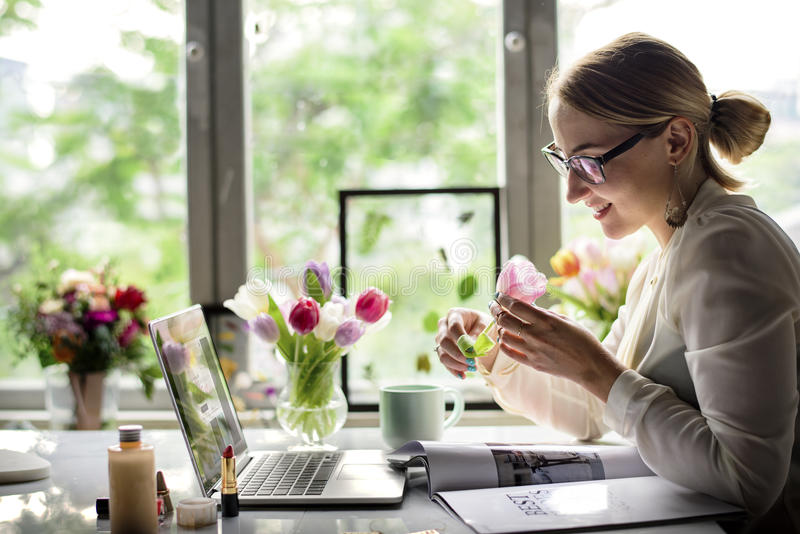 Businesswoman Holding Tulip Flower at Office Desk stock photo