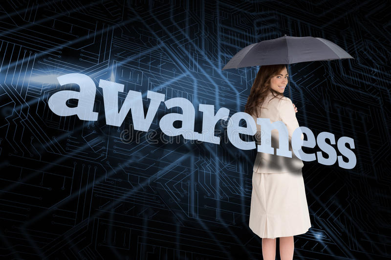 Businesswoman holding umbrella behind the word awareness. Against circuit board royalty free stock image