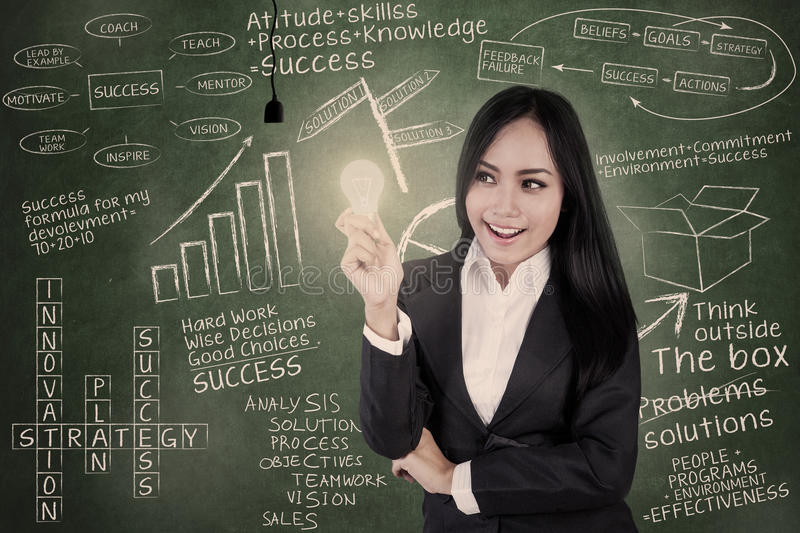 Download Businesswoman Holds Lit Bulb In Class Stock Photo - Image: 28162240