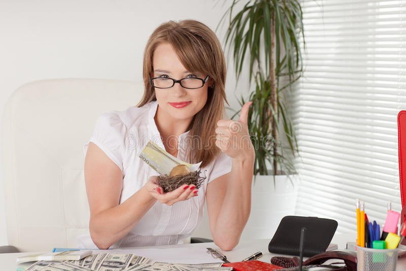Businesswoman holds nest with golden egg, money. royalty free stock image