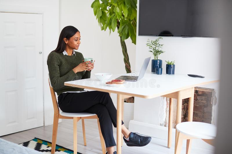 Businesswoman At Home Eating Breakfast Looking At Laptop Before Leaving For Work stock photography