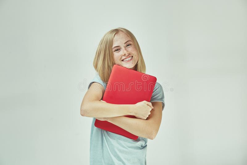 Businesswoman hugging laptop. Love to computer concept. Attractive female half-length front portrait. Trendy blue studio backgroud. Young emotional pretty royalty free stock photography