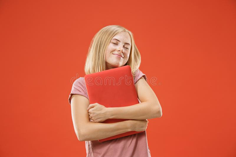 Businesswoman hugging laptop. Love to computer concept. Attractive female half-length front portrait. Trendy red studio backgroud. Young emotional pretty woman stock images
