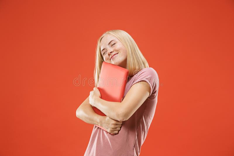 Businesswoman hugging laptop. Love to computer concept. Attractive female half-length front portrait. Trendy red studio backgroud. Young emotional pretty woman stock image