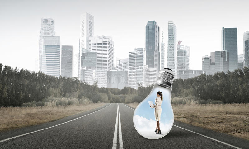 Businesswoman inside light bulb. Young businesswoman trapped inside of light bulb on asphalt road stock photo