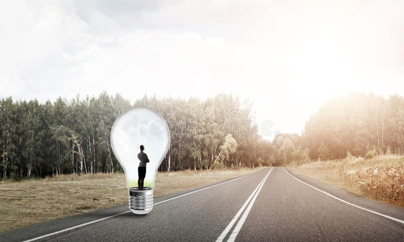 Businesswoman inside light bulb. Young businesswoman trapped inside of light bulb on asphalt road royalty free stock photo