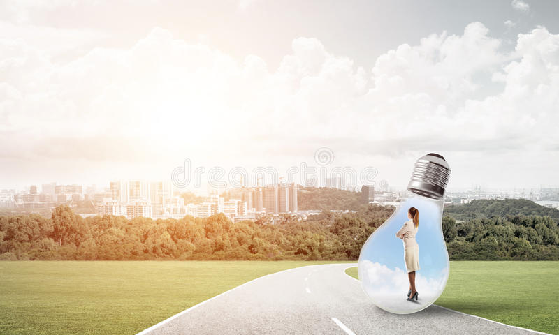 Businesswoman inside light bulb. Young businesswoman trapped inside of light bulb on countryside road royalty free stock image